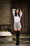 Fashion pretty young woman posing outdoor. Near a old wooden wall. Beautiful brunette with sensual lips in stockings Royalty Free Stock Photos