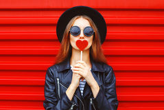 Fashion pretty young woman with red lollipop heart wearing black hat leather jacket over background. Fashion pretty young woman with red lollipop heart wearing Stock Images