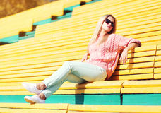 Fashion pretty young woman resting on bench Royalty Free Stock Photos