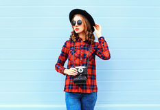 Fashion pretty young woman with retro camera posing wearing a black hat, red checkered shirt over blue background Stock Photos