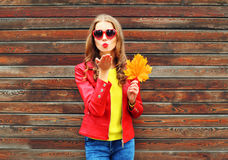 Fashion pretty young woman sends air sweet kiss with yellow maple leafs in autumn day over wooden background wearing red leather Royalty Free Stock Image