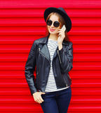 Fashion pretty young woman talking on smartphone wearing black rock style over colorful red Stock Image