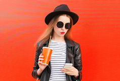 Fashion pretty young woman using smartphone in rock black style over colorful red. Background Royalty Free Stock Photos
