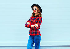 Fashion pretty young woman wearing black hat, red checkered shirt over blue. Background Stock Photo