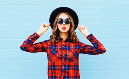 Fashion pretty young woman wearing black hat, red checkered shirt over blue background. Fashion pretty young woman wearing a black hat, red checkered shirt over Royalty Free Stock Photography