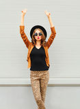 Fashion pretty young woman wearing a black hat, sunglasses and jacket raises hands up over urban background Stock Photo