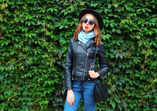 Fashion pretty young woman wearing black rock jacket, hat and bag over green leaves wall. Fashion pretty young woman wearing black rock jacket, hat and bag over Stock Photos