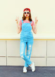 Fashion pretty young woman wearing a denim jumpsuit over white Royalty Free Stock Photo