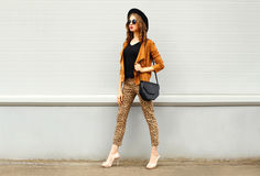 Fashion pretty young woman wearing a retro elegant hat, sunglasses, brown jacket and black handbag walking in city over backg Royalty Free Stock Photo