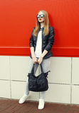 Fashion pretty young woman wearing a rock black leather jacket, sunglasses and bag over red Royalty Free Stock Image