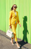 Fashion pretty young woman in yellow suit clothes with handbag Stock Photography