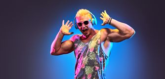 Fashion pumped-up DJ Music nightclub party concept. Fashion Excited Muscular DJ man dance music, colorful neon light. Handsome pumped-up blonde expressive guy royalty free stock photography