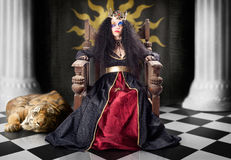 Fashion queen in crown sitting in jester court Royalty Free Stock Photography
