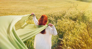 Fashion red hair woman standing back hands up with green fabric royalty free stock photos