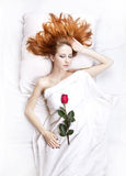 Fashion red-haired girl with rose in the bedroom. Royalty Free Stock Photos