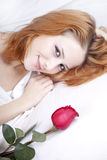 Fashion red-haired girl with rose in the bedroom. Stock Images