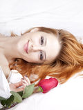 Fashion red-haired girl with rose in the bedroom. Stock Photo