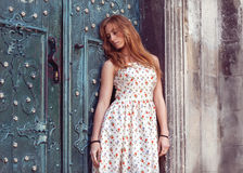 Fashion red-haired girl standing near a blue wall Royalty Free Stock Photography