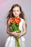 Fashion red-haired girl with tulips in hands. Studio photo on light coloured background. Birthday, holiday, mother`s day, first d royalty free stock image