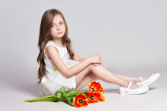 Fashion red-haired girl with tulips in hands. Studio photo on light coloured background. Birthday, holiday, mother`s day, first d stock photo