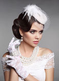 Fashion Retro elegant woman portrait. Wedding hairstyle. Brunette bride model present white hat, gloves and pearls jewelry access. Ories over gray studio stock photos