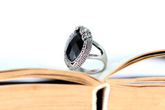 Fashion ring with black gem on a book pages Stock Images