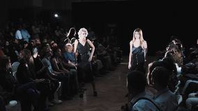 Fashion runway wmodel girls couple in black dresses walking and posing stock video footage