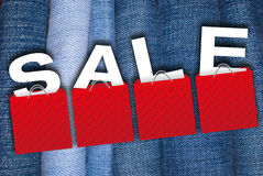 Fashion Sale. Sale Sign - Illustration of Red Shopping Bags With Letters on the Blue Jeans Background royalty free stock photos