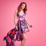 Fashion Sensual Redhead Girl. Summer Floral Dress. Sensual Sexy Redhead woman in Fashion Trendy Floral summer Dress Smiling. Beauty Model in fashion pose Stock Photography