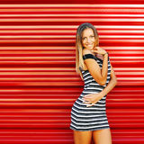 Fashion sensual woman posing on red wall background.  Royalty Free Stock Image