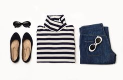 Fashion set of blue jeans, striped sweater, shoes and sunglsses. On white background. Selective focus Royalty Free Stock Photography