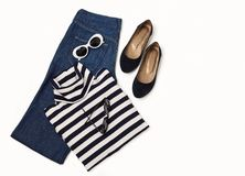 Fashion set of blue jeans, striped sweater, shoes and sunglsses. On white background. Selective focus Royalty Free Stock Images