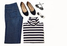 Fashion set of blue jeans, striped sweater, shoes and sunglsses. On white background. Selective focus Stock Photography