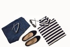 Fashion set of blue jeans, striped sweater, shoes and sunglsses. On white background. Selective focus Royalty Free Stock Photo