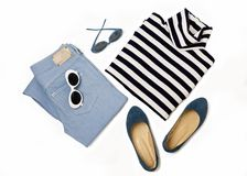 Fashion set of blue jeans, striped sweater, shoes and sunglsses. On white background. Selective focus Stock Photo
