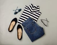 Fashion set of blue jeans, striped sweater, shoes and sunglsses. Flat lay. Top view Stock Photo