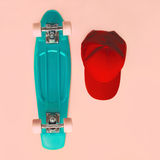 Fashion set. Skateboard and baseball cap on pink background Stock Image