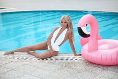 Fashion blond model woman in white bikini posing on Pink in royalty free stock photography