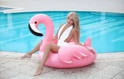 Fashion blond model woman in white bikini posing on Pink in. Flatable flamingo by swimming pool ring, tube, float. Summer vacation holiday luxurious resort royalty free stock photos