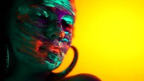 Fashion dancer in neon light. Fluorescent makeup glowing under ultraviolet light. Night club, party, halloween