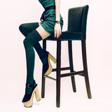 Fashion sexy lady in stockings and high heels. Sitting on bar stool Stock Images