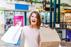 Fashion shocked young girl portrait. Beauty Woman with craft paper bags in Shopping Mall. Shopper. Sales. Shopping Center. Space f Royalty Free Stock Photography