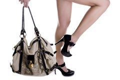 Fashion shoes and bag. Long girl's legs on high heels with fashion bag Stock Image