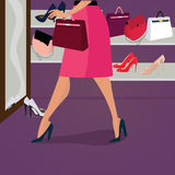 Fashion shoes and bags. Premium quality fashion shoes and bags for women in shop. Attractive woman in a red skirt looks in the mirror and trying bag.nBeautiful Royalty Free Stock Images