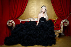 Fashion shoot of beautiful blond  woman in a long black dress sitting on sofa Stock Photography