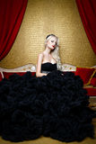 Fashion shoot of beautiful blond  woman in a long black dress sitting on sofa Royalty Free Stock Photography