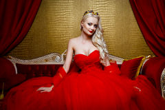 Fashion shoot of beautiful blond woman in a long red dress sitting on sof Stock Image