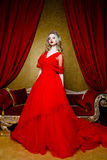 Fashion shoot of beautiful blond woman in a long red dress on vintage red sofa background Stock Photos