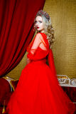 Fashion shoot of beautiful blond woman in a long red dress on vintage red sofa background Royalty Free Stock Image