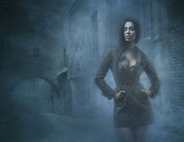 Fashion shoot of a young and brunette in fog Stock Photography